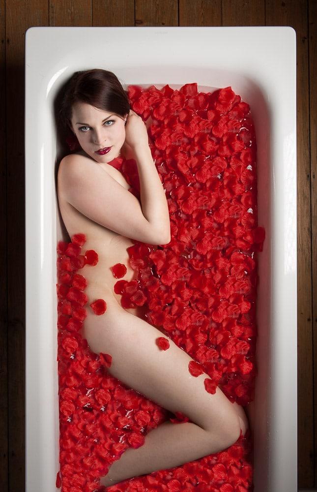 Frau in Badewanne mit Rosenblüten
