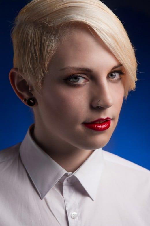 Portrait einer blonden Frau vor blauem Hintergrund im Fotostudio