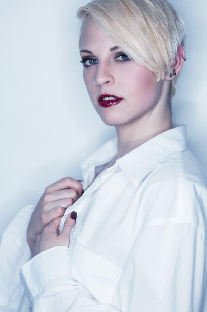 Blonde Frau vor weißem Hintergund im Fotostudio