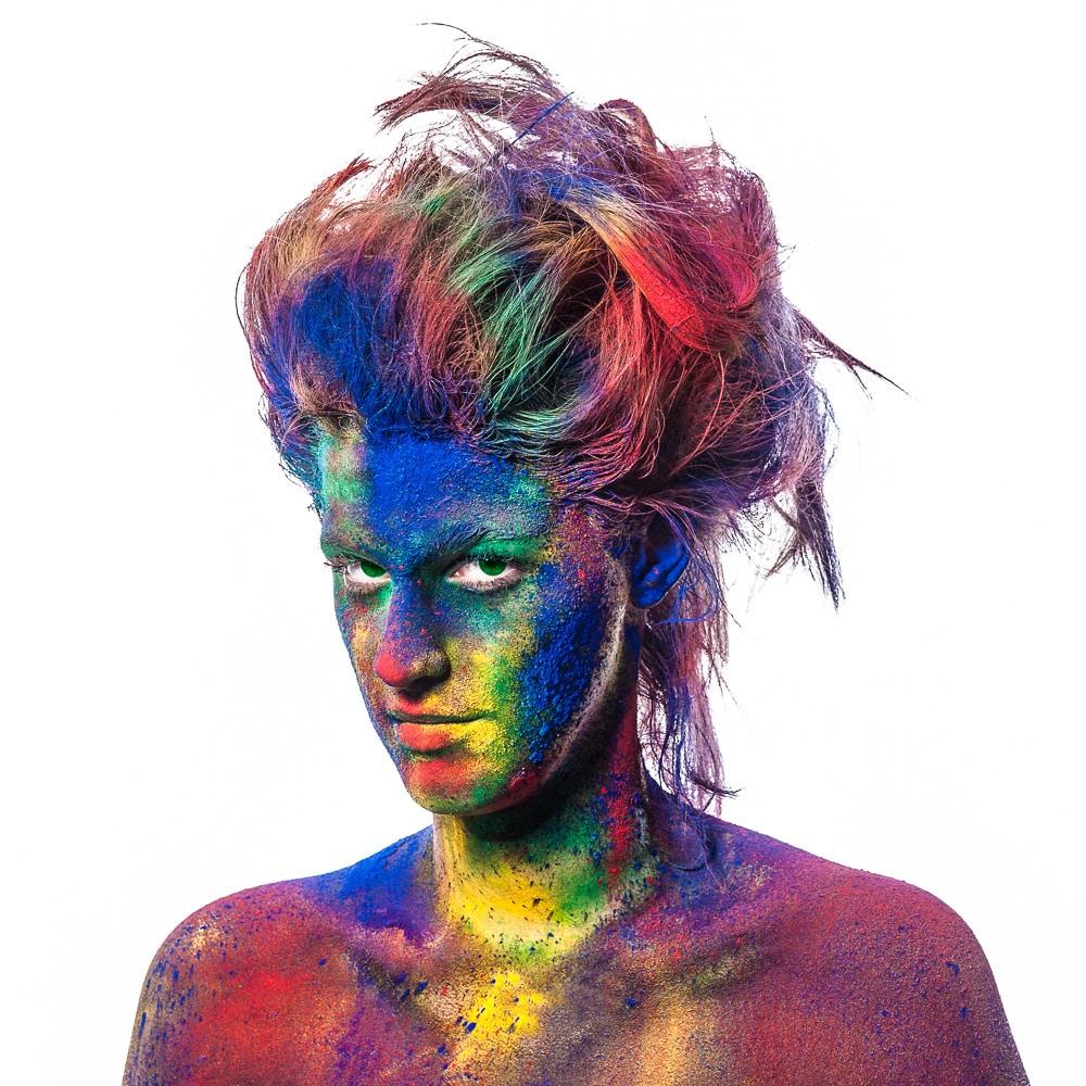 Frau mit bunten Farben im Gesicht im Fotostudio