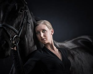 Frau posiert vor schwarzem Pferd