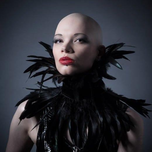 Frau mit Glatze und Federkragen im Fotostudio