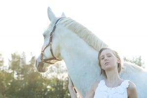 gegenlicht-portrait einer Frau mit weißem Pferd