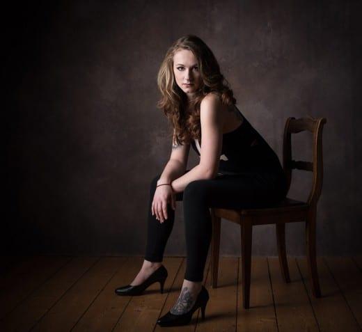 Portrait einer Frau auf einem Stuhl im Fotostudio