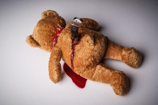 Teddybär mit Messer im Rücken und Blut