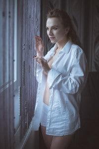 Frau im Hemd an Fenster