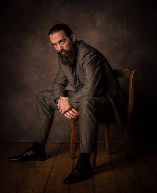 Portrait-Foto von Mann im Anzug auf Stuhl