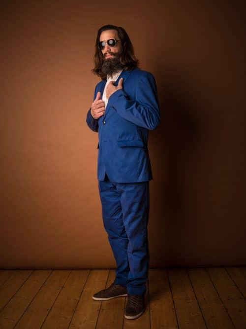 Foto von Mann im blauen Anzug vor braunen Hintergrund