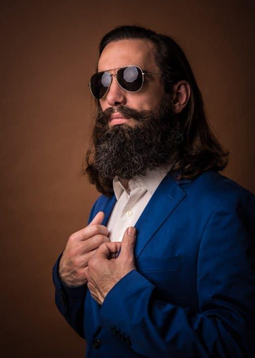Portrait-Foto von mann im blauen Anzug vor braunen Hintergrund