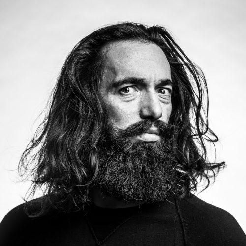 Portrait-Foto von Mann mit Bart vor weißem Hintergrund