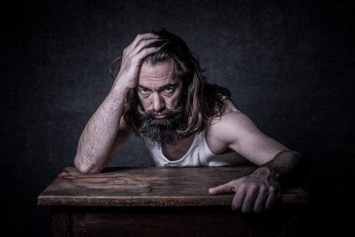 Portrait-Foto von Mann mit Bart am Tisch