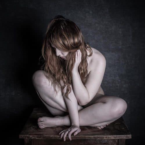 Frau sitzt nackt auf Tisch