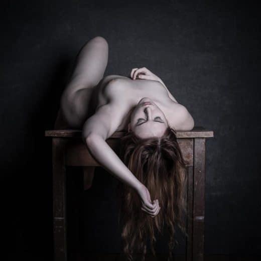 Frau liegt nackt auf Tisch