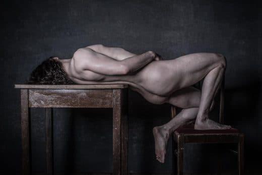 Mann liegt nackt auf Stuhl und Tisch