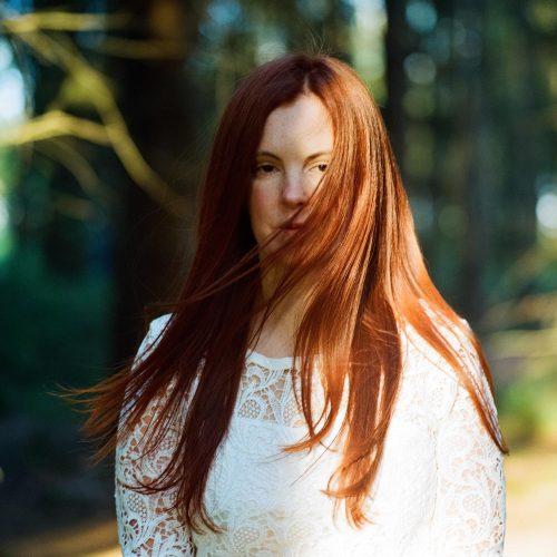 Analoges Portrait einer rothaarigen Frau im Wald