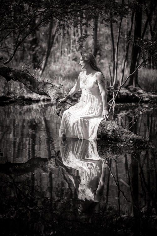 Frau im weißen Kleid sitzt auf Baum