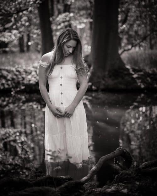 Frau steht mit weißem Kleid im Teich