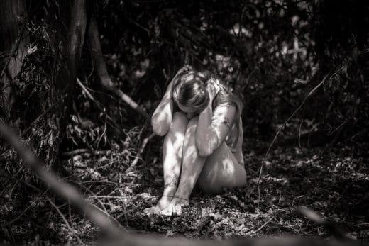 Nackte Frau hockt auf Boden im Wald