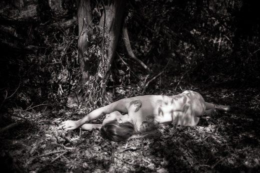 Akt von liegender Frau im Wald
