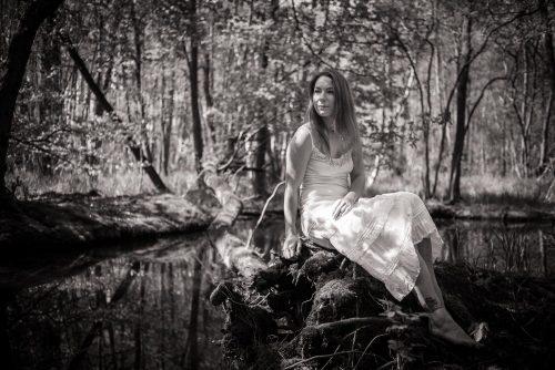 Frau im weißen Kleid am Teichufer