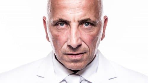 Highkey-Portrait eines Mannes mit Glatze im weißen Anzug vor weißem Hintergrund